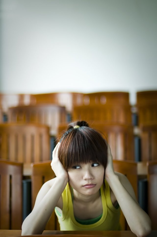 Irritated Freestockphotos dot biz 9442-a-beautiful-chinese-girl-sitting-tired-at-a-desk-pv